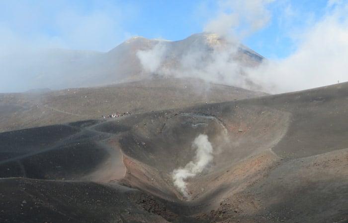 Uno de los cráteres turísticos con el principal del Etna al fondo