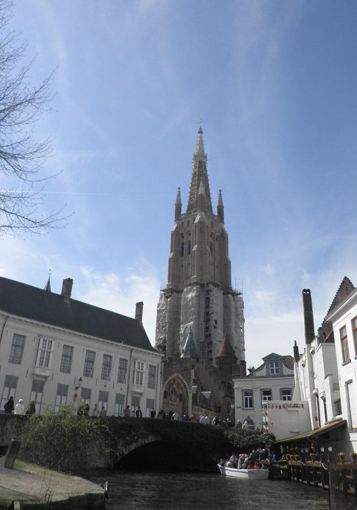 Torre de la iglesia de Nuestra Señora desde uno de los canales qué ver en Brujas en un día