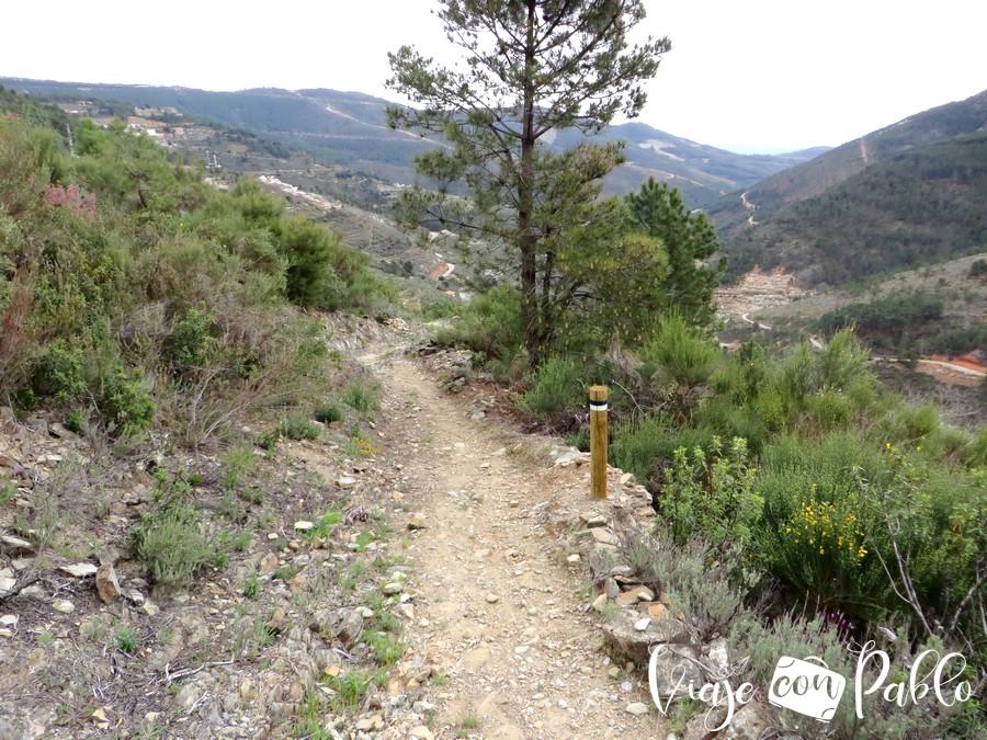 Senda de descenso a Huetre marcadas con estacas con los colores verde y blanco