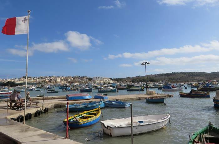 Vista del puerto de Marsaxlokk y un grupo de pescadores charlando