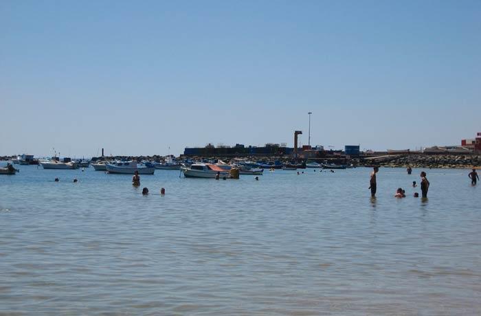 Bañistas y pequeño puerto pesquero junto a la playa de Las Teresitas