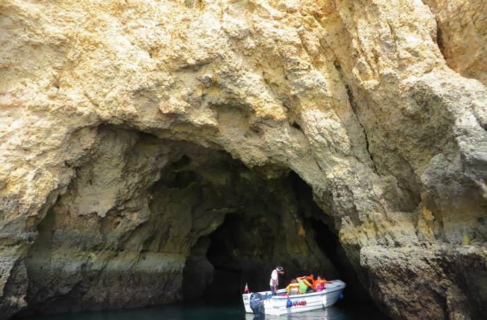 Una barca introduciéndose en una de las grutas de Lagos