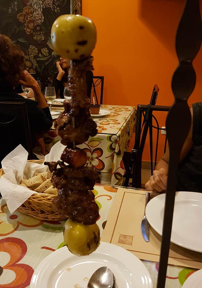Espeto de carne de cerdo con manzana asada comer en Coimbra