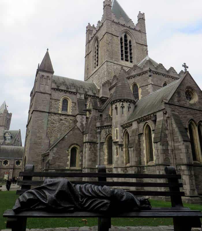 """Escultura """"Homeless Jesus"""" de Timothy Schmalz junto a Christ Church Dublín en un día"""