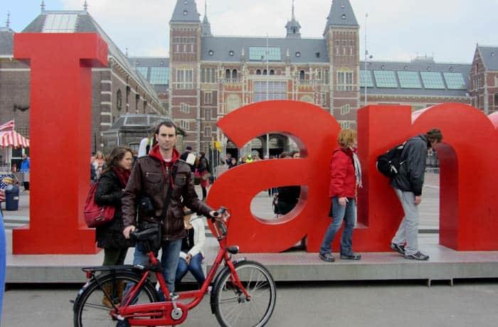 Pablo posando con la bicicleta delante las letras de I amsterdam
