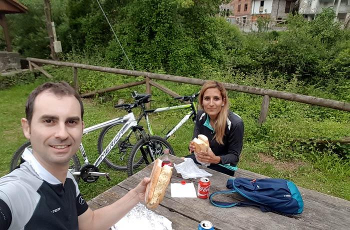 Comiendo un bocadillo de tortilla junto al puente de piedra de Villanueva Senda del Oso en bici