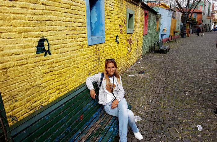 Estefanía, sentada en un banco de Caminito visitar La Boca