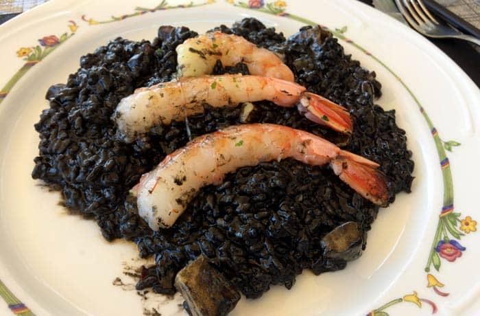 Arroz negro con sepia y gambas servido en su plato comer en Menorca