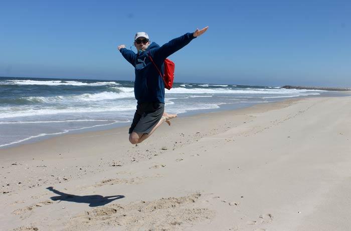 Saltando en la arena de la playa de Costa Nova