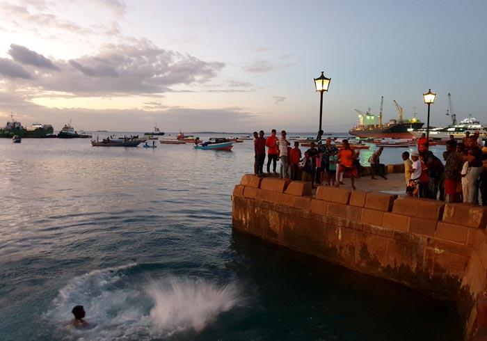 Saltos al agua al tardecer en el paseo marítimo de Stone Town